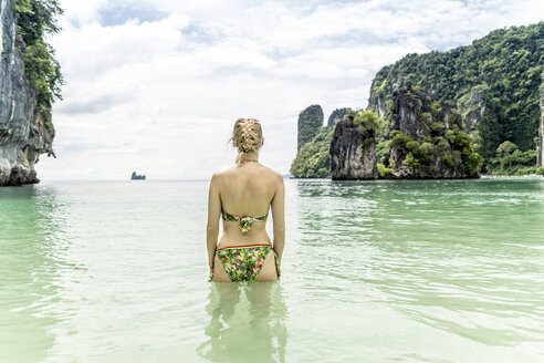 Thailand, Ko Hong, back view of woman standing in the sea looking to horizon - CHPF00473
