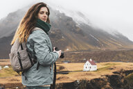 Iceland, portrait of hiker with backpack and camera - KKAF00996