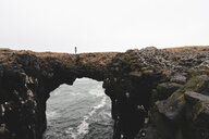 Iceland, Arnarstapi, woman standing on rock arch - KKAF01002