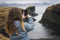 Iceland, back view of young woman taking picture with smartphone at coast - KKAF01011