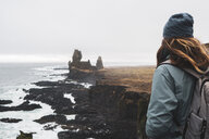 Iceland, Snaefells, National Park Snaefellsjoekull, Londrangar, back view of woman looking at coast - KKAF01014
