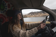Iceland, young woman driving van - KKAF01020