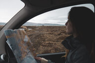 Iceland, young woman in car looking out of window - KKAF01032