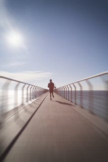 Man running along a promenade around the sea - SKCF00455