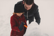 Father and daughter making snowman - ISF04598
