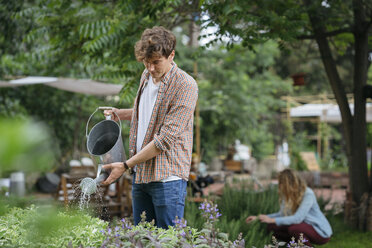 Young man and woman tending to plants in urban garden, man watering plants using watering can - ISF04652