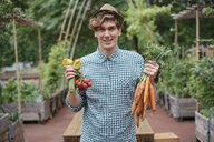 Man in garden holding bunches of carrots smiling - ISF04676