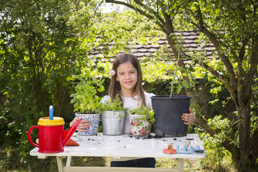 Portrait of proud little girl with potted spice plants on table in the garden - LVF06996