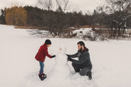 Father and daughter making snowman - ISF04740