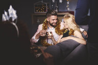 Man and woman at party, sitting on sofa, holding drinks, making a toast - ISF04761