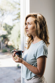 Young woman with coffee gazing at patio door - ISF04824