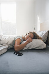 Smartphone on bed, young woman asleep - ISF04827