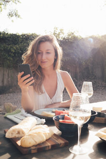 Portrait of young woman, outdoors, sitting at table with prepared food, using smartphone - ISF04833