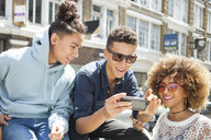 Three young friends outdoors, looking at smartphone - ISF04866