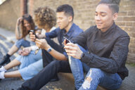 Four friends sitting in street, looking at smartphones - ISF04878