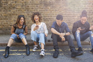 Four friends sitting in street, laughing, young woman holding smartphone - ISF04881