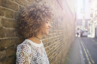 Young woman leaning against wall, smiling - ISF04887