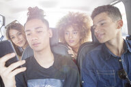Four friends in taxi, looking at smartphone - ISF04890