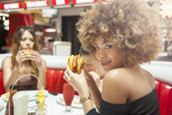 Three young friends, sitting in diner, eating burgers - ISF04893
