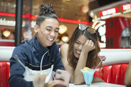 Young couple sitting in diner, looking at smartphone, laughing - ISF04899