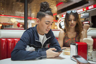 Young couple, sitting in diner, young man looking at smartphone, woman with bored expression - ISF04938