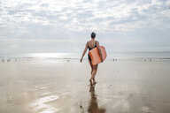 Woman carrying surfboard on beach, Folkestone, UK - ISF05043