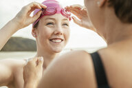 Mother and daughter adjusting swimming goggles on beach, Folkestone, UK - ISF05049