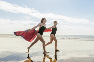 Mother and daughter running on beach with shawls in air, Folkestone, UK - ISF05055