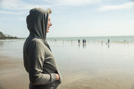 Woman on beach in hooded top, Folkestone, UK - ISF05064