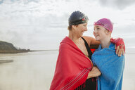 Mother and daughter standing on beach with shawls, Folkestone, UK - ISF05115