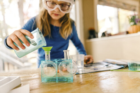 Girl doing science experiment, pouring liquid into flask - ISF05181