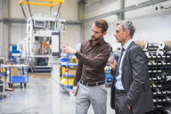 Businessmen in factory having discussion - ISF05355
