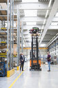 Manager looking up at forklift truck in distribution warehouse - ISF05367
