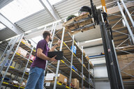Warehouse worker looking up at forklift pallet in distribution warehouse - ISF05370