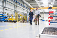 Colleagues walking through factory - ISF05430