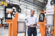 Mature male engineer looking at digital tablet in engineering factory - ISF05442
