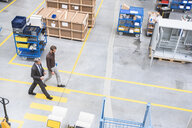 High angle view of supervisor and manager walking through distribution warehouse - ISF05445