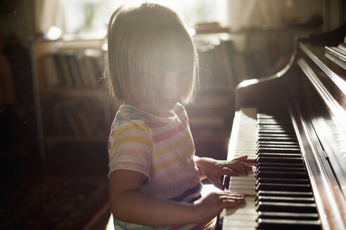 Girl at home playing old piano - ISF05460