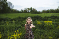 Portrait of girl with wavy blond hair punching in field - ISF05466