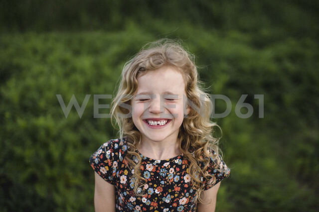 Portrait of girl with wavy blond hair and missing tooth in field - ISF05469 - Erin Lester/Westend61
