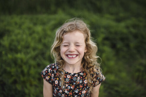 Portrait of girl with wavy blond hair and missing tooth in field - ISF05469