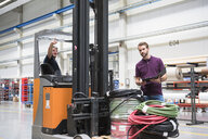Forklift truck driver pointing in distribution warehouse - ISF05502