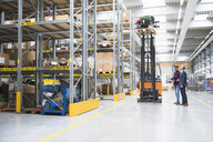 Manager looking up at forklift truck in distribution warehouse - ISF05505