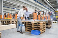 Two engineers looking at product in engineering factory - ISF05511