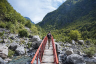 Rear view of man crossing bridge, Accursed mountains, Theth, Shkoder, Albania, Europe - ISF05520
