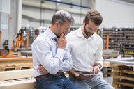 Two engineers looking at digital tablet in engineering factory - ISF05559