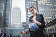 Businesswoman using mobile phone, Canary Wharf, London, UK - ISF05607