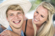 Young couple laughing together at beach party - ISF05682
