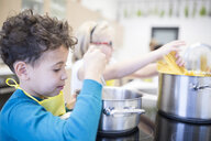 Pupils preparing pasta in cooking class - WESTF24077