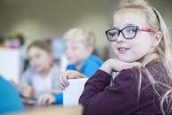 Portrait of smiling schoolgirl with classmates in class - WESTF24083